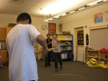 Mr. Kawaragi teaching a student at Greely Middle School the traditional Japanese toy, sudare.